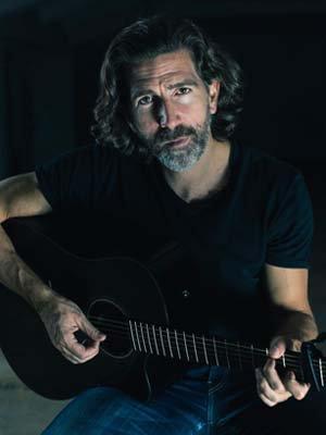 Porträtfoto von Dr. Timo Eifert mit Gitarre